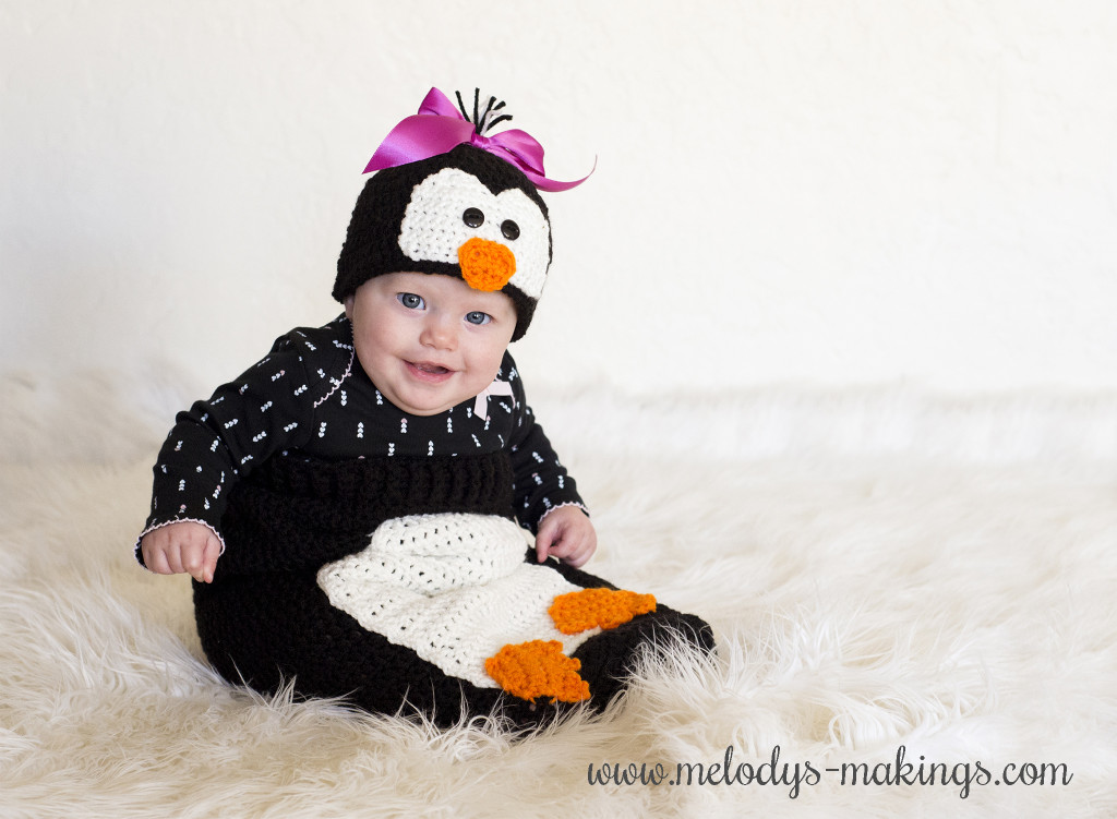Baby dressed as penguin in crochet outfit